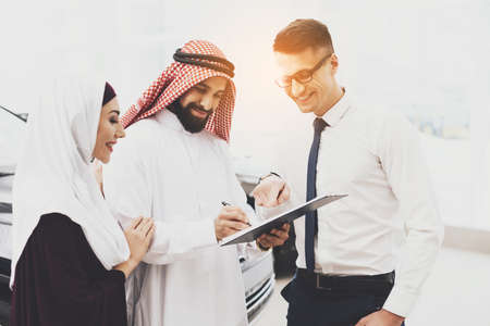 Arab smiles while puts a signature on purchase.