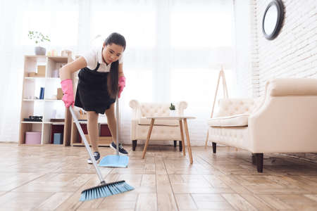 A cleaning lady in a special uniform sweeps floor.