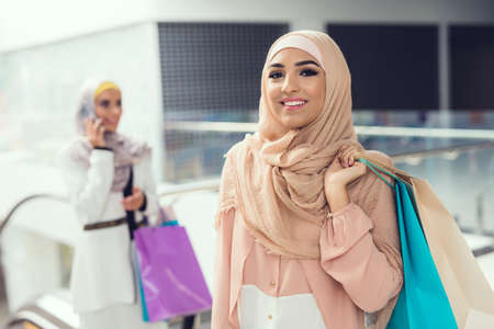 Arabian Women with Cups of Coffee Standing in Mall
