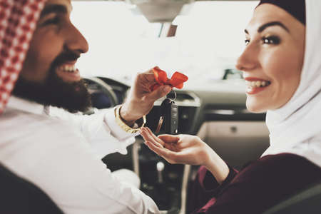 Arab man gives his new car keys to his wife.