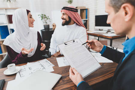 Male Arabs woman sit at the table at the realtor.