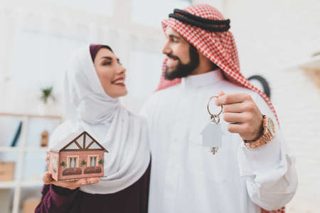 Woman looking at arab man while holding house. 免版税图像