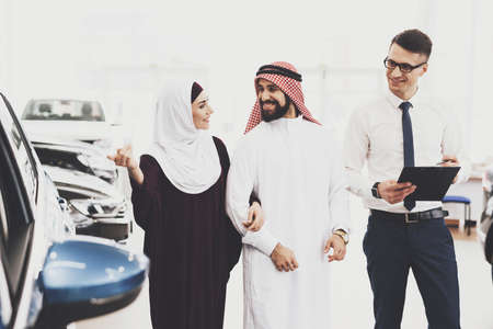 Arab smiles while looking at a big car.