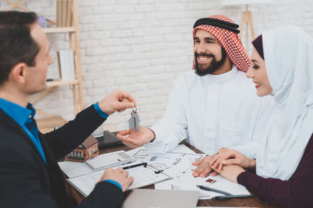 Arabs sit at table with realtor and buy apartment. 免版税图像