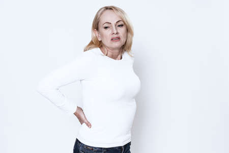 Woman on a white background suffers from back pain