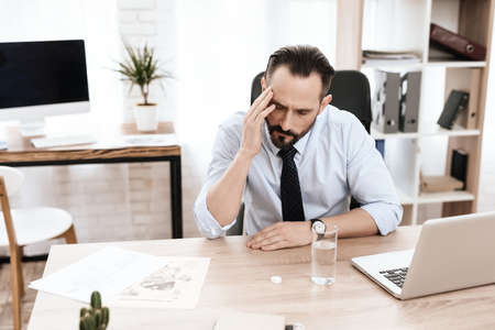 A man sits at wooden table and works at computer. Stock fotó