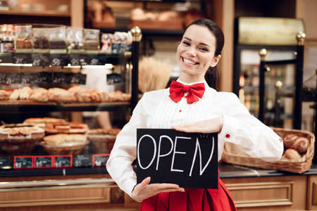Young Woman with Open Sign Standing in Bakery. Zdjęcie Seryjne