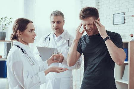 Doctors look at a suffering sportsman in office. Standard-Bild
