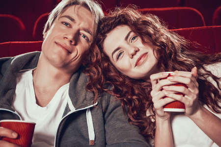 Red haired girl with boyfriend watching movie.