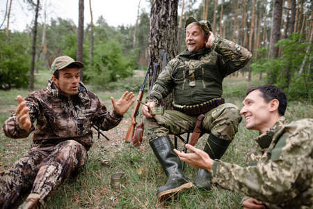 Drunk Hunters Have Picnic Telling Funny Story. Stockfoto