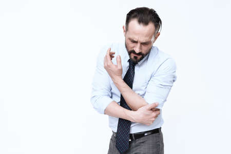 A man with a beard feels pain in the elbow.