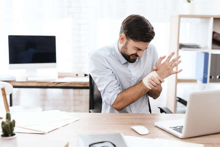Man suffers and hold on to a sore wrist at work.