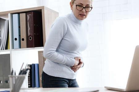 A white woman has a stomach ache. Stock fotó