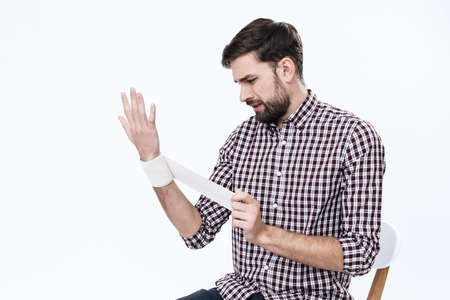 A man in a shirt sits and makes a bandage.