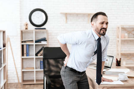 Man in office grabbed his sore back and suffers.