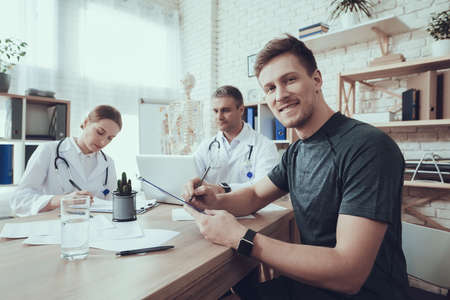 A male athlete sits at doctor office and signs. Standard-Bild