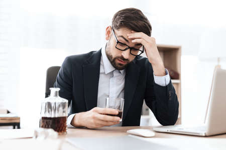 Man drinking an alcoholic drink in the workplace.