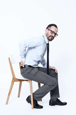 A man in shirt sits on chair and hold on sore back Stockfoto