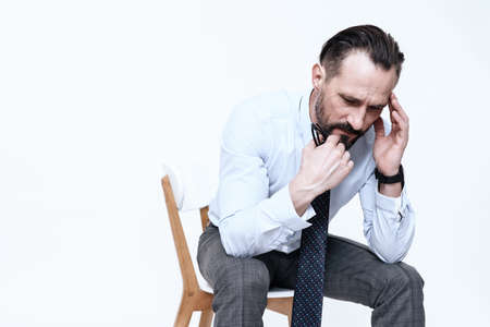 A man in a shirt sits and feels pain in his head.
