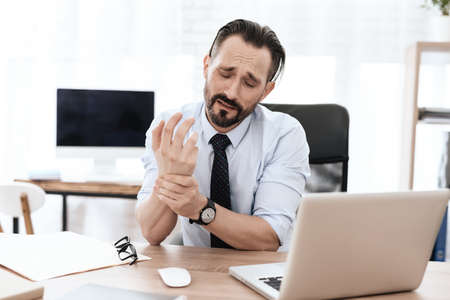 Man sitting at work and holding on to sore wrist. Stockfoto