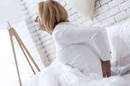 A woman with a sore back gets up in the morning.