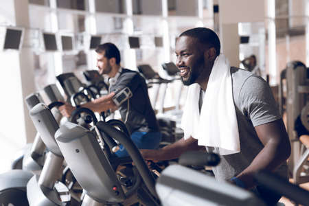 Two men are engaged on treadmills in modern gym.