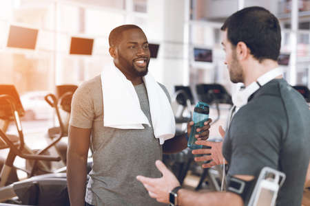 Two men communicate at racetracks in modern gym.