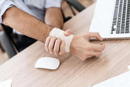 A male injured hand lies on table at a computer.