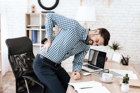 Man holding on to side while standing in an office