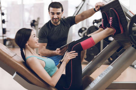 Trainer helps sportswoman in exercise.