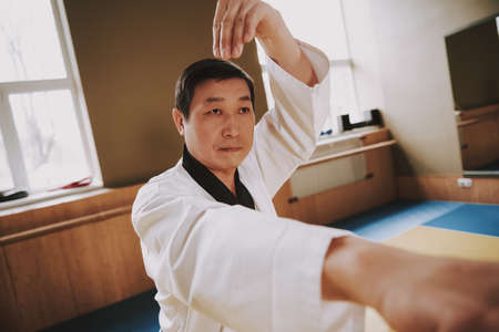 Chinese man practicing karate at karate school.