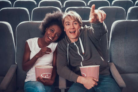 Multinational couple is watching comedy in cinema.