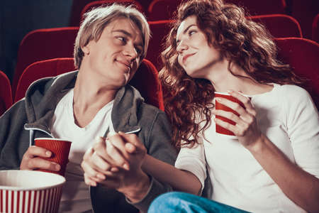 Loving couple sit holding hands in cinema. Imagens