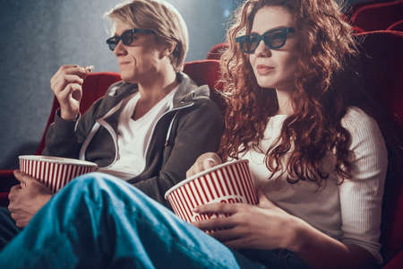 Beautiful woman with a man sitting in the cinema.