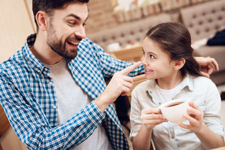 Father with Daughter Eating Cakes in Cafeteria. Imagens