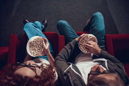 Blond guy with red haired girl eating popcorn.