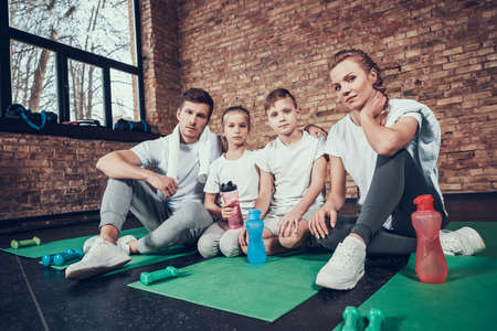 Sport Family Sit On Gym Carpet During A Break.