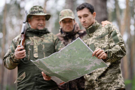 Topographical Map in Hands of Hunters in Forest.