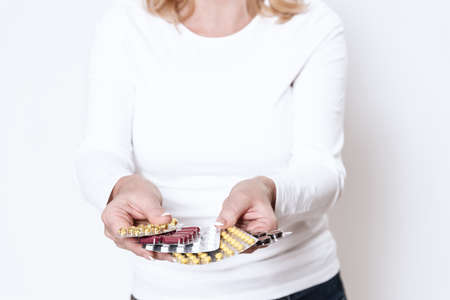 Adult woman with pills in her hands.