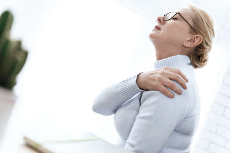 A woman holding on to her shoulder that hurts.