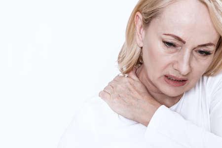A woman has a sore neck.