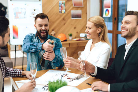 Bearded man opens champagne with colleagues. Banque d'images