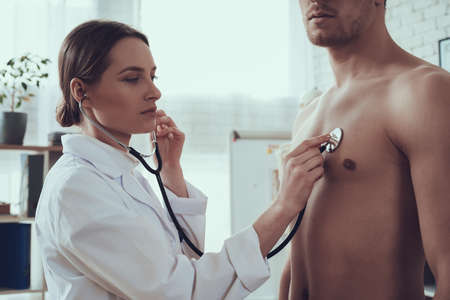 Doctor listens to a male athlete with stethoscope.