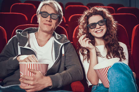 Guy and woman are sitting and watching a movie 写真素材