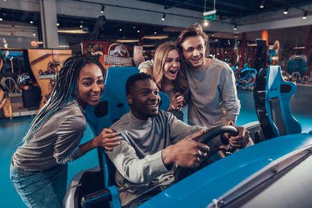 Black man smiling and driving car in playroom.