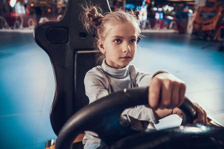 Girl sitting behind the wheel of a game machine. 写真素材
