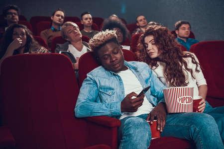A man closes phone to his girlfriend at cinema.