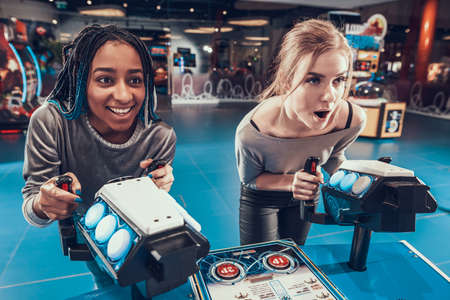 Young girls enthusiastically play video games.