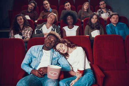 Multiethnic couple in love is sleeping in cinema.