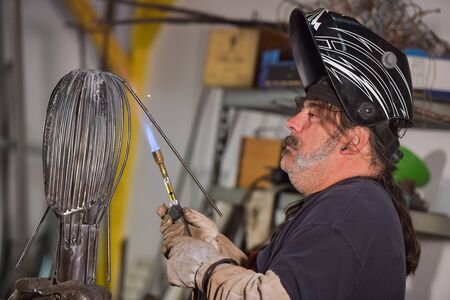 blowtorch: Blowtorch worker-Metal worker in workshop Stock Photo